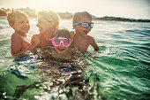 Mother with her three kids aged 7 and 10 are having fun splashing in sea waves. Family is having lovely tome todether. Candid smile and laughter. Sunny summer vacations day at sea.