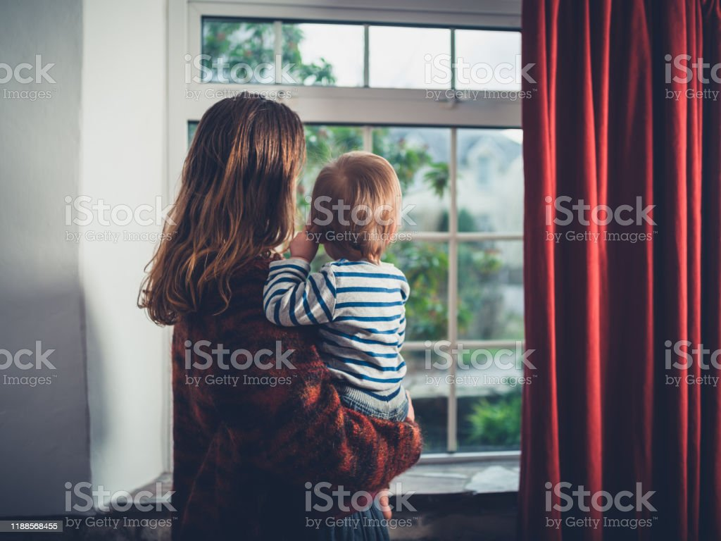 Mother with toddler by the window A young wmother is looking out the window with her little toddler boy Adult Stock Photo
