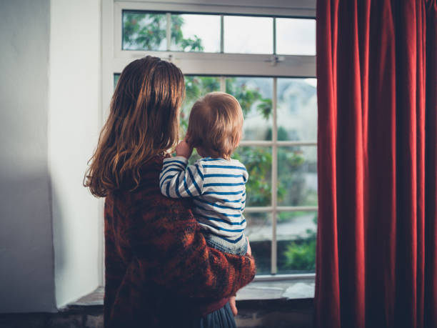 Mother with toddler by the window stock photo