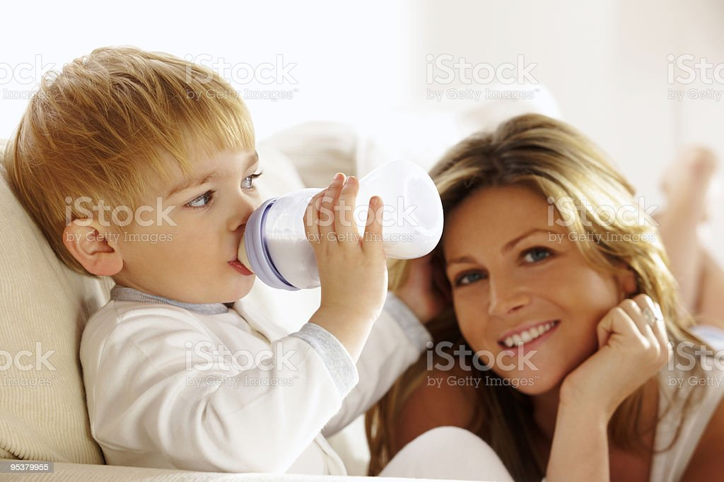 Mother with toddler drinking milk from a bottle at home royalty-free stock photo