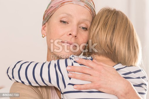 637119208 istock photo Mother with tumor hugging child 836562700