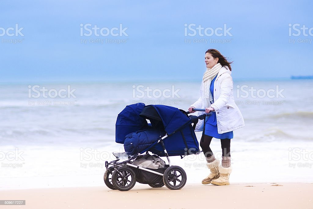 Mother with twin stroller on a beach royalty-free stock photo