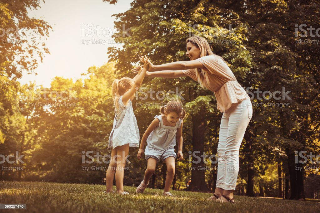 Mother with two child in meadow. Mother holding hands with girl other...