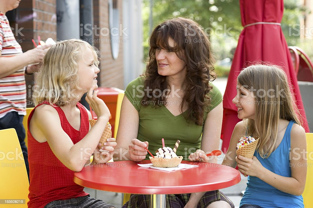 Mother with two children eating ice cream at table stock photo