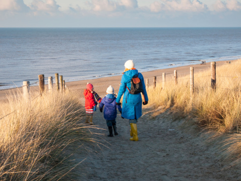 Mother with two children in winter waking over beach dunes