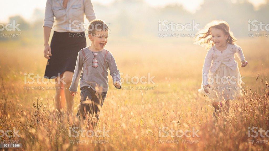 Mother with two children running in the nature stock photo