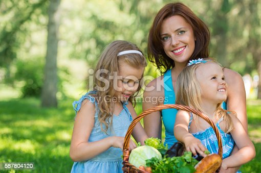 istock Mother with two daughters in the park 587804120