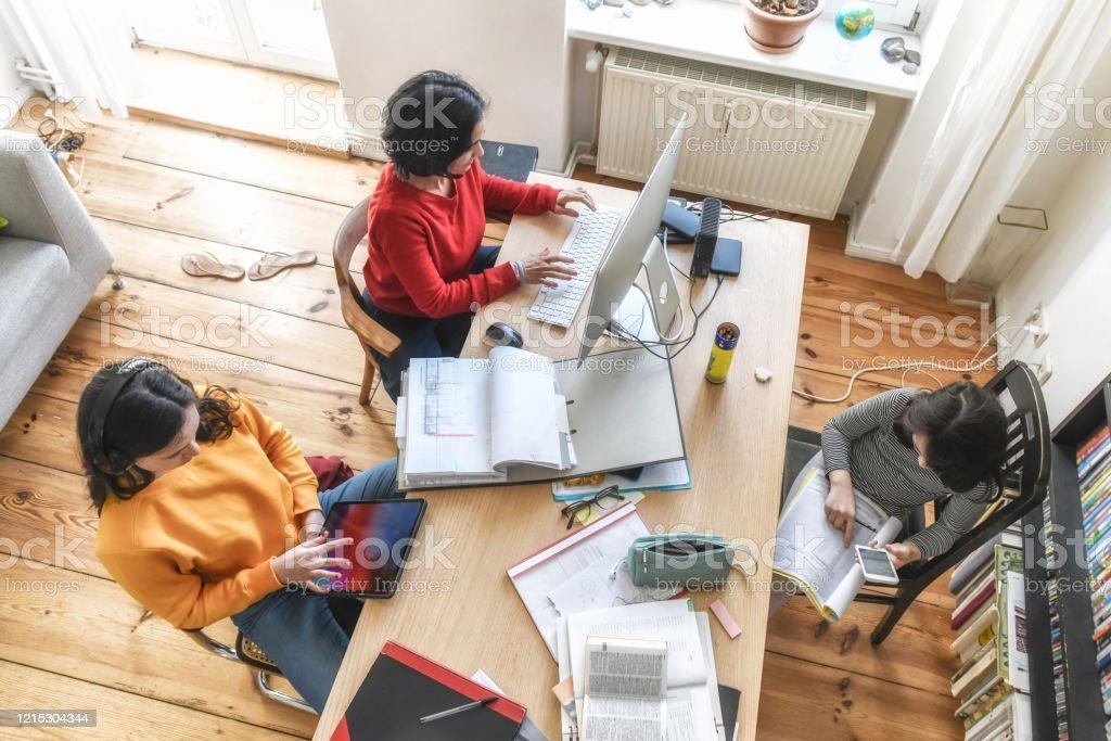 Mutter mit zwei Kindern, die zusammen am Schreibtisch im Homeoffice arbeiten - Lizenzfrei Abstand halten - Infektionsvermeidung Stock-Foto