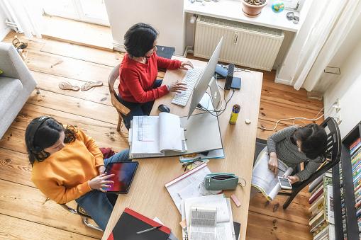 Mutter Mit Zwei Kindern Die Zusammen Am Schreibtisch Im Homeoffice Arbeiten Stockfoto und mehr Bilder von Abstand halten - Infektionsvermeidung