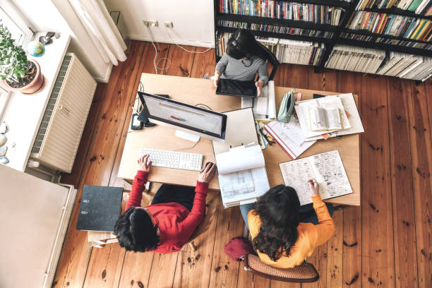 mother with two kids working together at desk in homeoffice stock photo