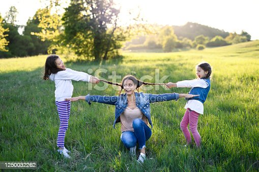 Front view of mother with two small daughters having fun outdoors in spring nature, pulling hair.