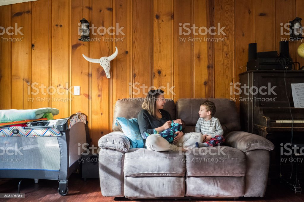 Mother with two sons on couch stock photo