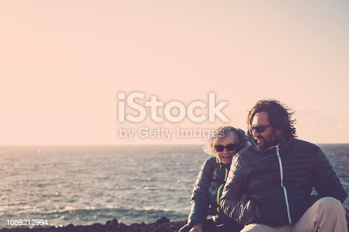 Mother with white hair and a 45 year old son spend time together smiling, surrounded by unspoiled nature. Between sea and mountain. ocean view in background for caucasian couple