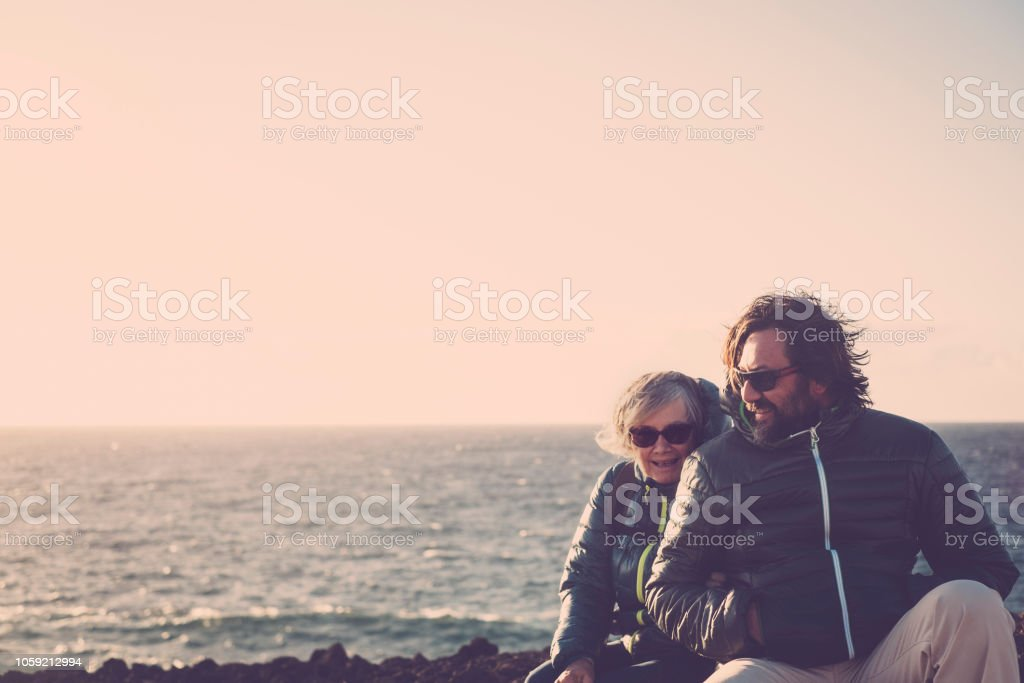 Mother with white hair and a 45 year old son spend time together smiling, surrounded by unspoiled nature. Between sea and mountain. ocean view in background for caucasian couple stock photo