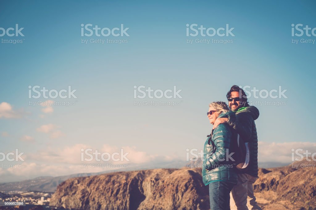 Mother with white hair and a 45 year old son spend time together smiling, surrounded by unspoiled nature stock photo
