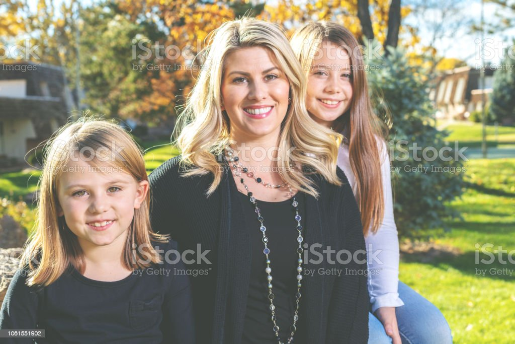 Mother with Young Elementary Aged Girl Outdoors in Autumn Happy Sisters in Western Colorado Park Area stock photo