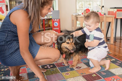 Baby boy stroking family pet and Aboriginal young woman crouching and smiling at him