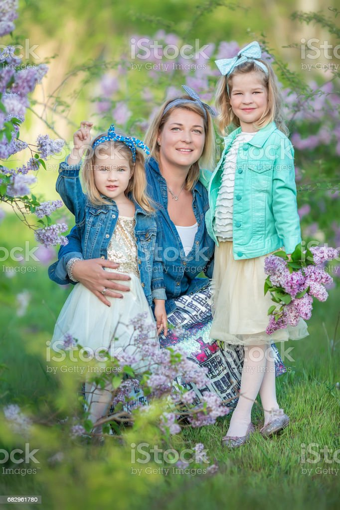 Mother woman with two cute smiling girls sisters lovely together on a lilac field bush all wearing stylish dresses and jeans coats royalty-free stock photo
