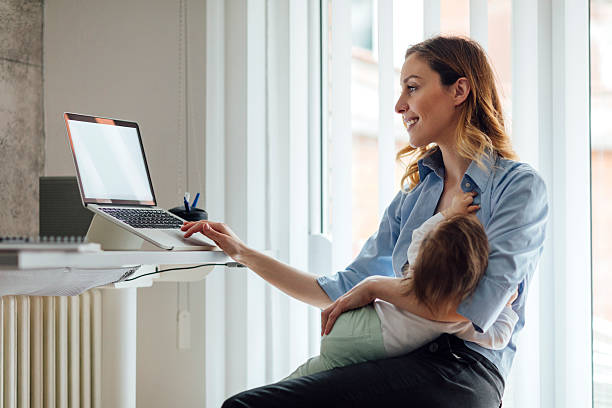 Mother Working and breastfeeding her baby stock photo