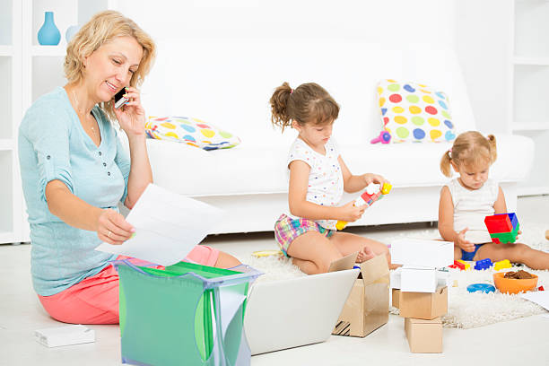 mother working at home with children. - happy mom packing some toys stock photos and pictures