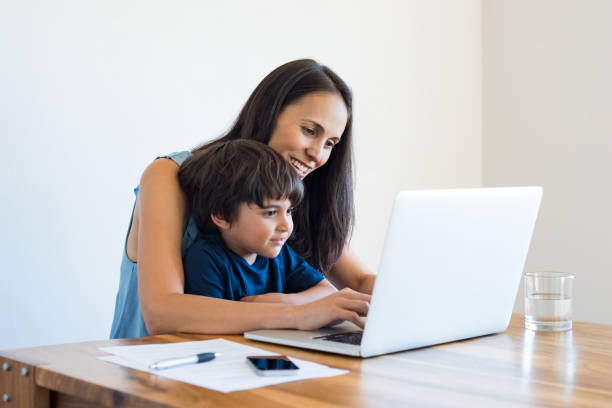Mother working at home with son stock photo