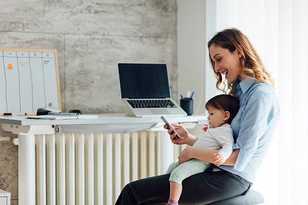 madre lavorando da casa e con il suo neonato - owner laptop smartphone foto e immagini stock