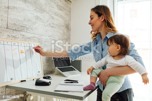istock Mother Working From Home And Holding Her Baby 515524676
