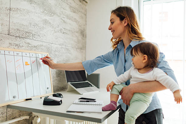 mère travaillant à la maison et tenant son bébé - femmes actives photos et images de collection