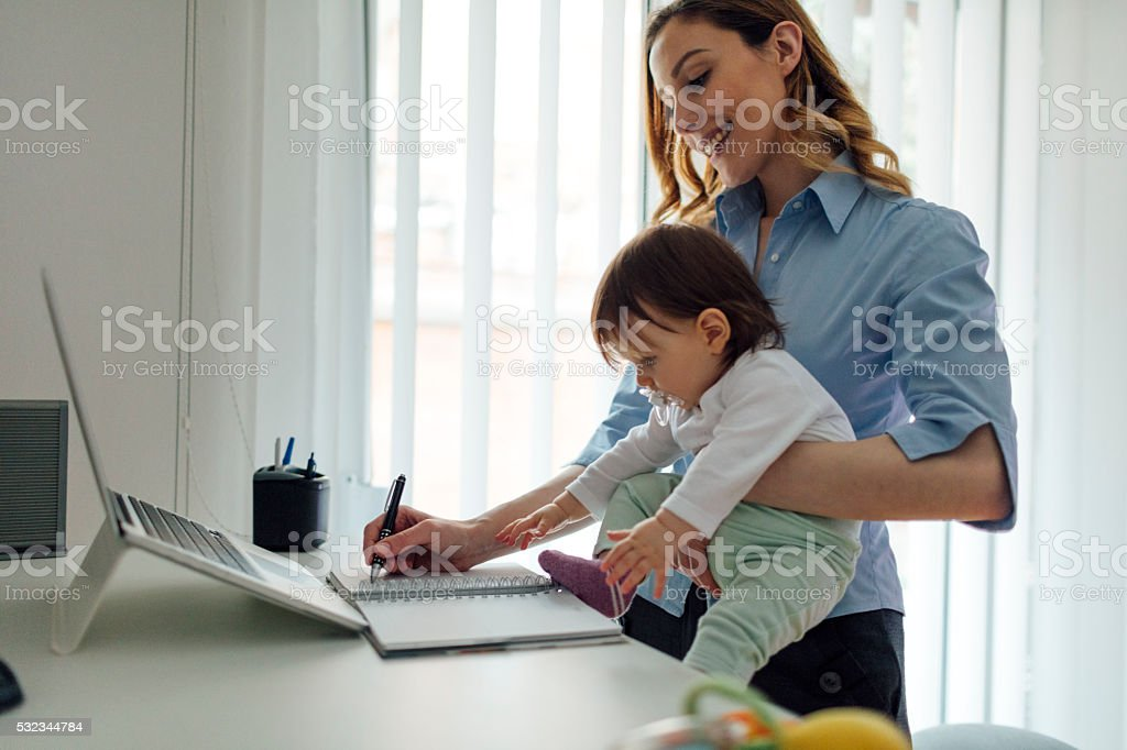 Mother Working From Home And Holding Her Baby stock photo