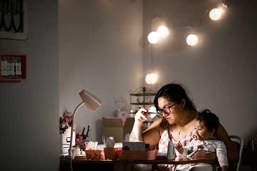 Authentic image of a mother working from home at her desk while holding her baby daughter. Shot in the late hours of the evening, the lighting creates the late night mood.