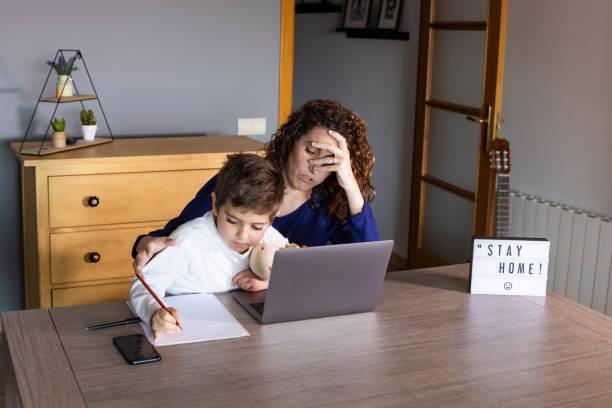mutter arbeitet von zu hause aus mit einem kind. quarantänemodus - homeschooling stock-fotos und bilder