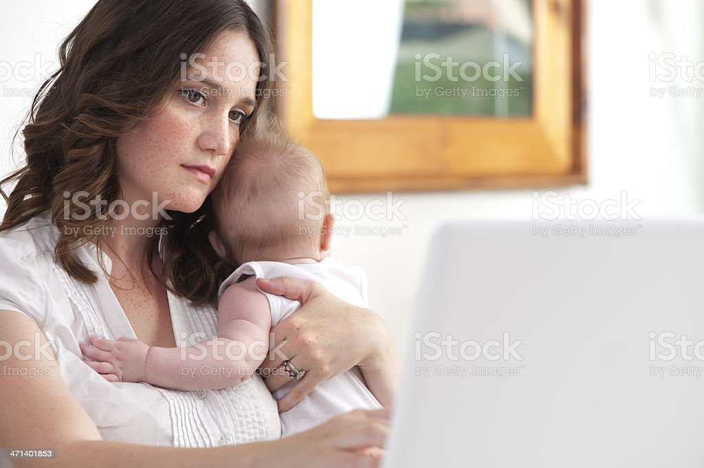 Mother working from home with baby stock photo