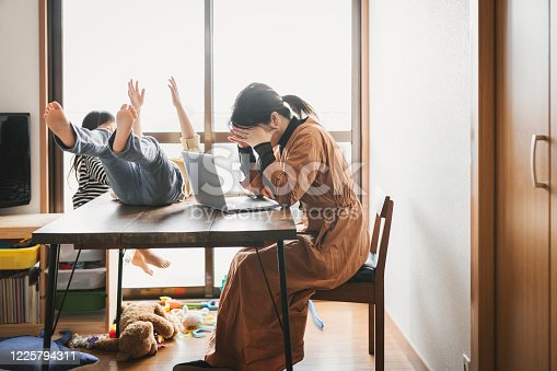 Asian mother working with laptop while her son and daughter are playing in the living room. Her son is playing on the table.