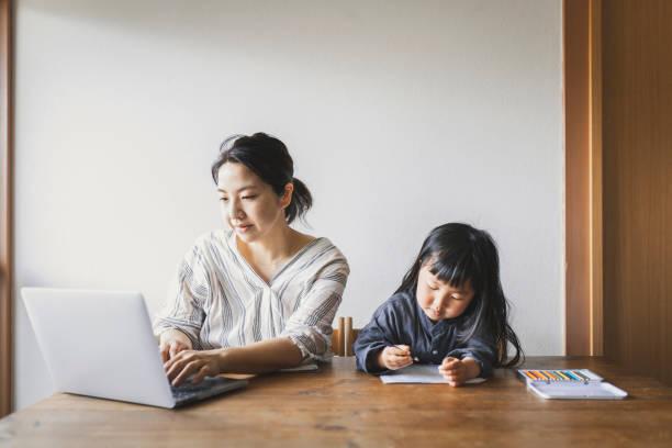 Mãe trabalhando em casa com a filha - foto de acervo