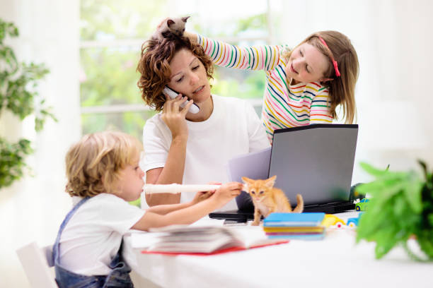 Mother working from home with kids. Quarantine. Mother working from home with kids. Quarantine and closed school during coronavirus outbreak. Children make noise and disturb woman at work. Homeschooling and freelance job. Boy and girl playing. quarantine stock pictures, royalty-free photos & images