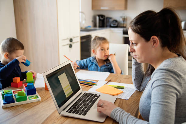 Mother working from home with young children in quarantine isolation Covid-19 stock photo