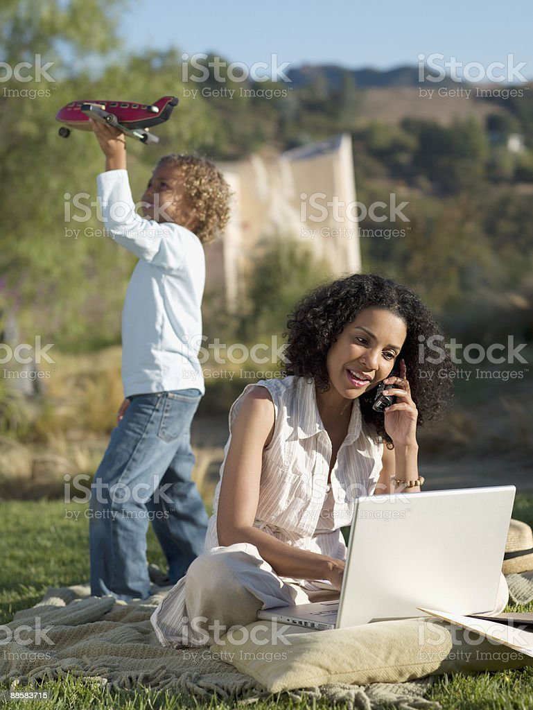 Mother working in park as son plays stock photo