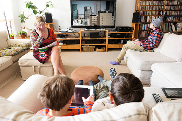 mother working on the phone at home with her family. - family watching tv stock photos and pictures