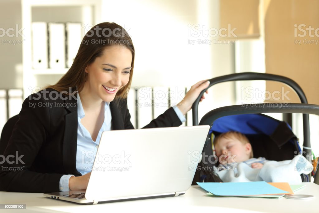 Mother working taking care of her baby at office stock photo
