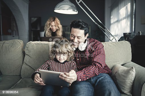 istock Mother working with laptop computer while father and son are using tablet at home 918696054