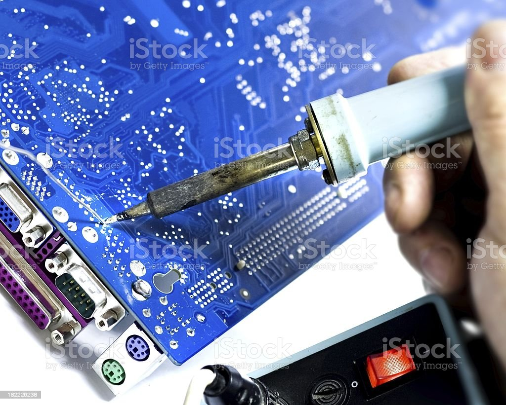 motherboard repair with soldering iron stock photo