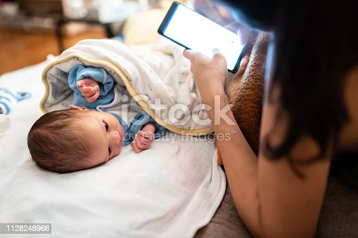 Close up of unrecognizable mother using smart phone while little baby lying on bed beside her