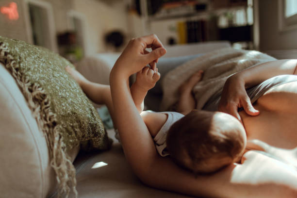 Motherhood Breastfeeding in the morning tranquil scene stock pictures, royalty-free photos & images