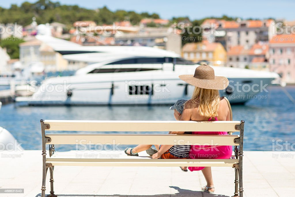 Motherhood Mother and a son sitting on the bench and looking at a boat docked in the port. The photo shows the beauty of the Island Losinj in Croatia 2015 Stock Photo