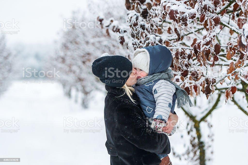 Motherkissing her daughter outdoor in winter stock photo