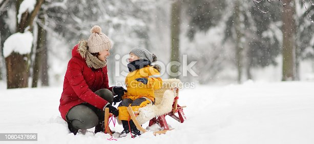 istock Mother/nanny talk with small child during sledding in winter park 1060437696