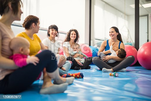 Group of mothers with their little babies on group exercise class with an instructor. Some of them breastfeeding their babies. Belgrade, Serbia
