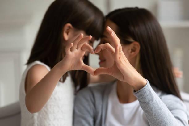 mothers and daughters fingers showing heart symbol of love - mano donna dita unite foto e immagini stock