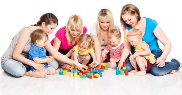 Mothers and Kids Group Playing Toys, Mother With Baby Play Building Blocks, White Background stock photo