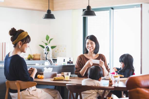 母親と子供がダイニング テーブルで食事 - 談笑する ストックフォトと画像
